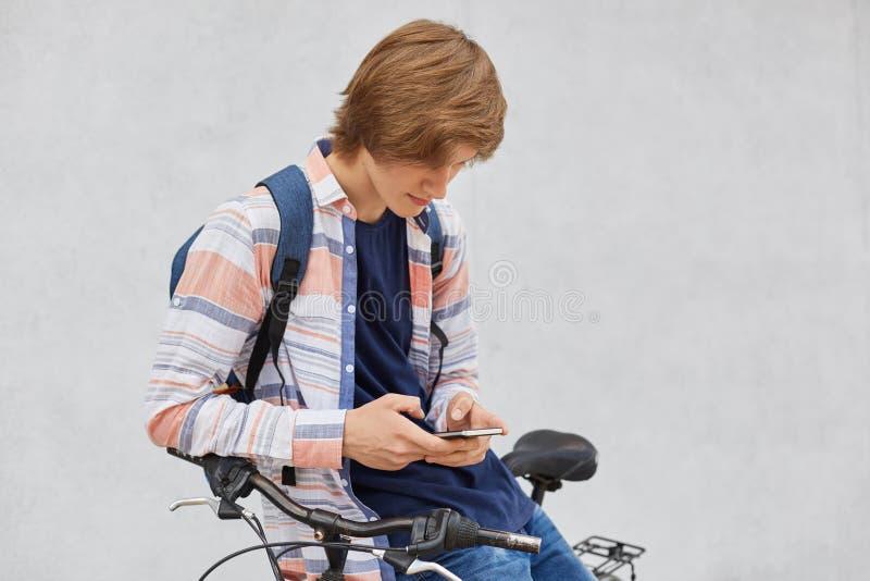 Porträt des Hippie-Kerls mit dem tragenden Hemd und Jeans der modischen Frisur, die den Rucksack steht nahe seinem Fahrrad unter  stockfotos
