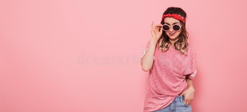 Porträt des Hippie-Mädchens in den Gläsern auf rosa Hintergrund stockfotos