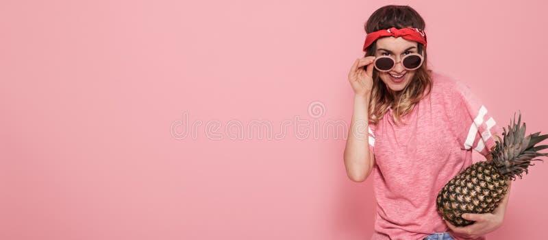 Porträt des Hippie-Mädchens in den Gläsern und in der Ananas auf rosa Hintergrund lizenzfreies stockbild