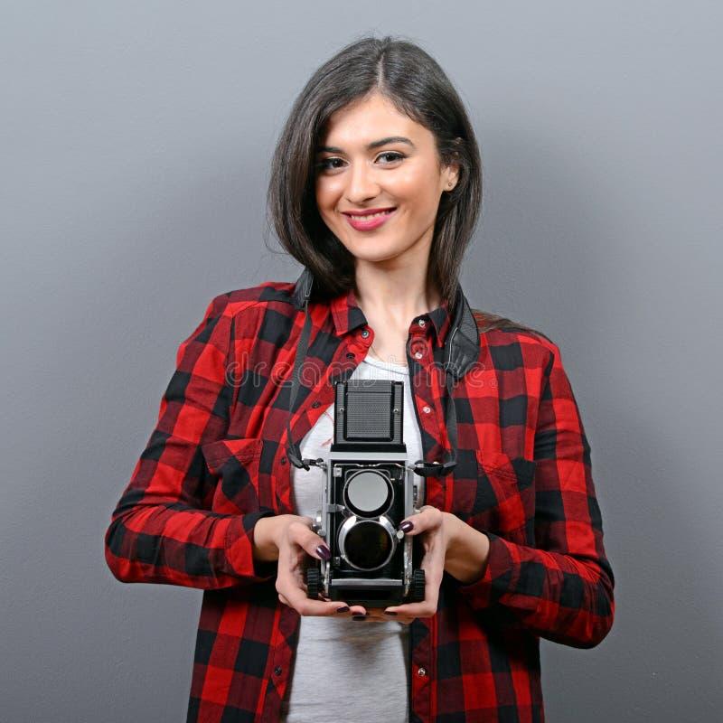 Porträt des Hippie-Mädchens mit Retro- Kamera gegen grauen Hintergrund stockfotografie