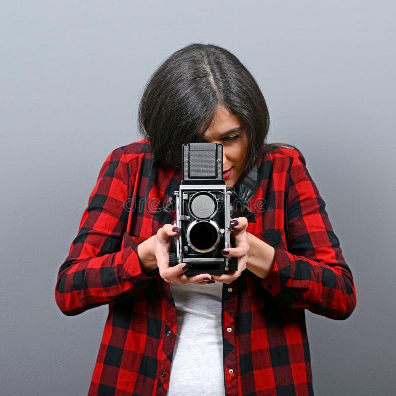 Porträt des Hippie-Mädchens mit Retro- Kamera gegen grauen Hintergrund lizenzfreie stockbilder