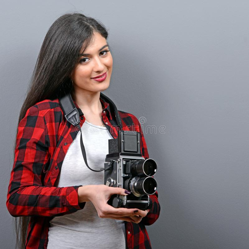Porträt des Hippie-Mädchens mit Retro- Kamera gegen grauen Hintergrund stockfoto