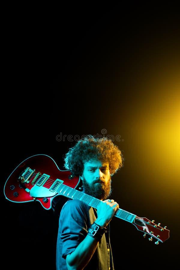 Portr?t des Hippie-Mannes mit dem gelockten Haar mit roter Gitarre in den Neonlichtern lizenzfreie stockbilder