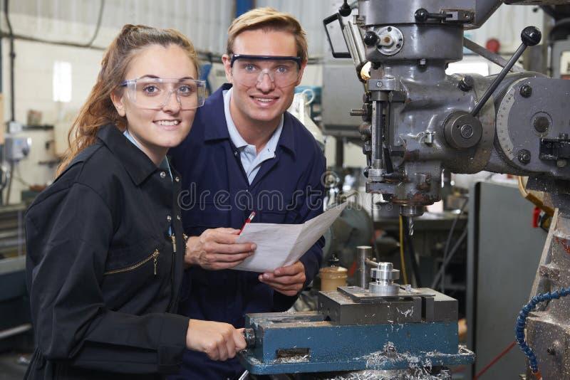 Porträt des Ingenieurs Showing Apprentice How, zum des Bohrgeräts tatsächlich zu benutzen stockfotografie