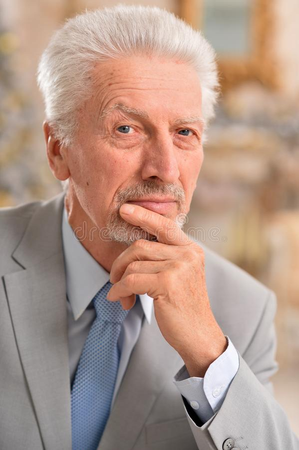 Porträt des intelligenten älteren Geschäftsmannes, der zu Hause denkt lizenzfreies stockbild