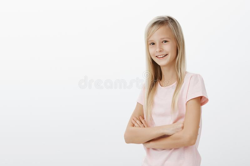 Porträt des intelligenten kreativen kleinen Mädchens mit dem angemessenen Haar, Händchenhalten, das gekreuzt wird und breit, Wart lizenzfreies stockfoto