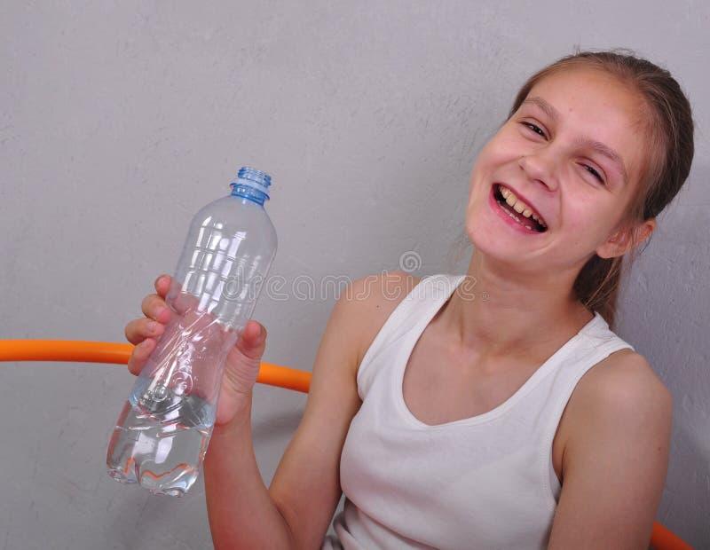 Porträt des jugendlich Mädchens des Sports mit einem Trinkwasser der Flasche lizenzfreie stockbilder