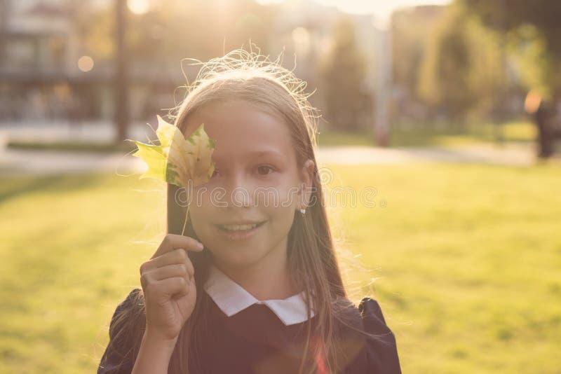 Porträt des jugendlich Mädchens mit Ahornblatt stockfotografie