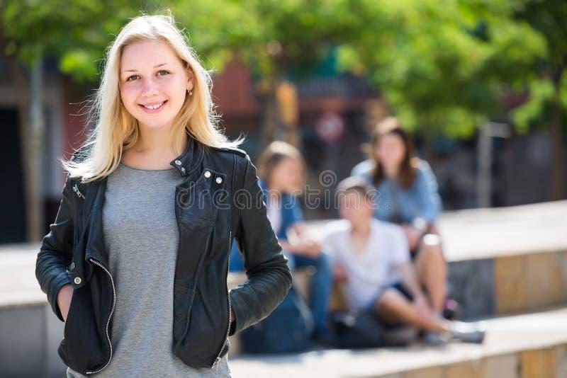 Porträt des Jugendlichmädchens draußen stehend neben Freunden stockfotografie
