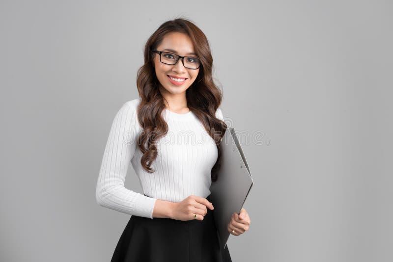 Porträt des jungen überzeugten asiatischen weiblichen Lehrers mit Ordner lizenzfreies stockbild