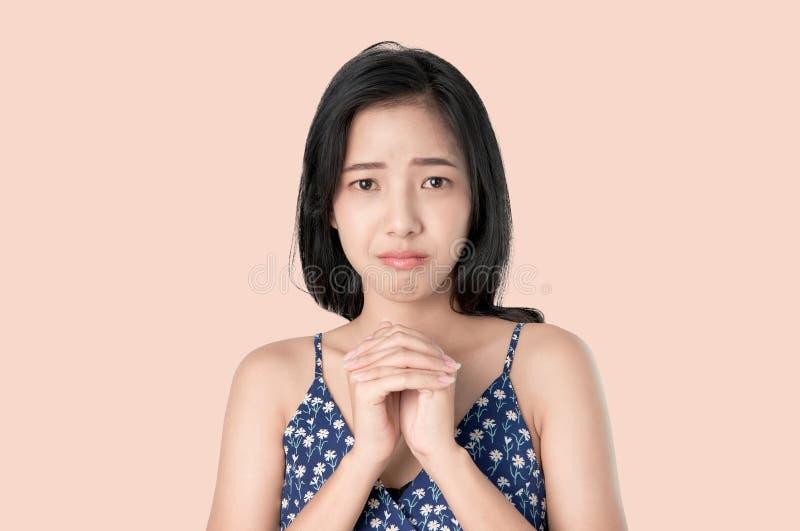 Porträt des jungen Asiatinstirnrunzelngesichtes wird schreien und die umklammerten Hände und hat irgendeinen Antrag auf hellem Hi stockbild