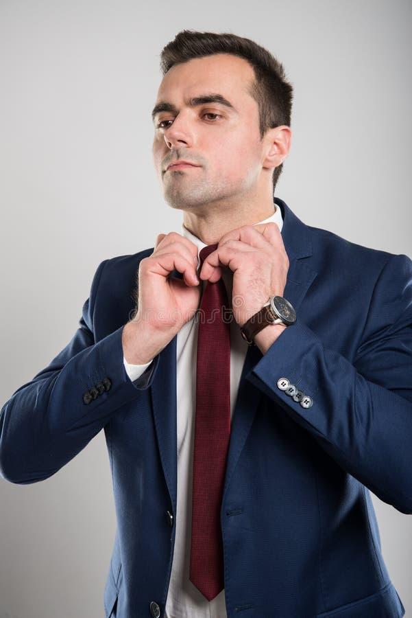 Porträt des jungen attraktiven Geschäftsmannes, der seinen Kragen vereinbart lizenzfreie stockbilder