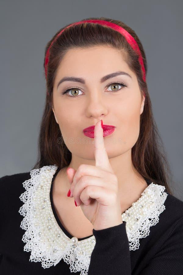 Porträt des jungen attraktiven Mädchens mit dem Finger auf ihren Lippen stockfotografie