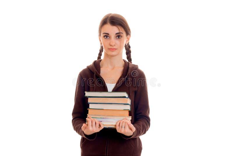 Porträt des jungen attraktiven Studentenmädchens im braunen Sport kleidet mit vielen Büchern in den Händen, die auf Weiß lokalisi lizenzfreies stockbild