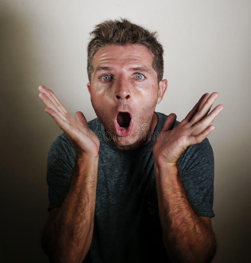Porträt des jungen attraktiven und überraschten Mannes, der in den Schock und in Ungläubigkeit überspielen in entsetzter Handgest lizenzfreie stockfotos
