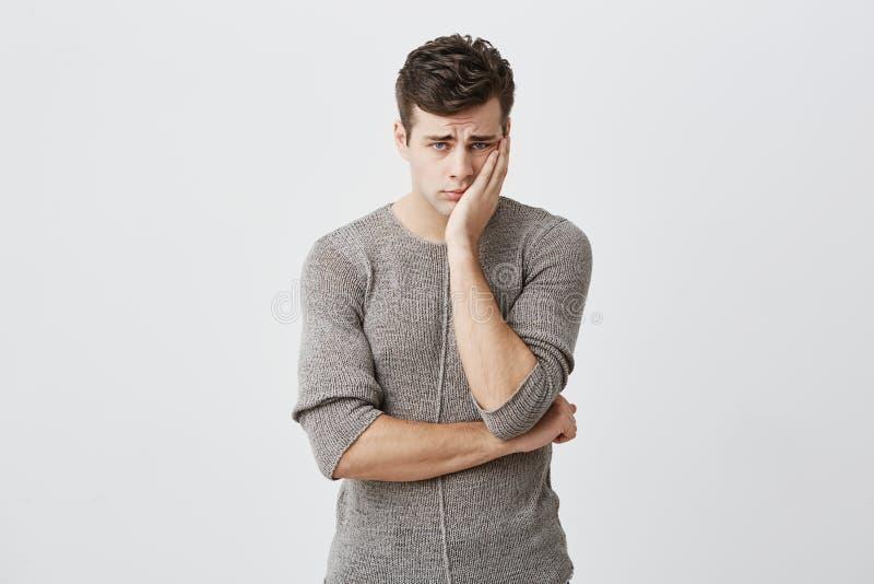Porträt des jungen blauäugigen Mannes des traurigen Umkippens mit dem dunklen Haar, tragende Strickjacke, Hand auf der Backe halt lizenzfreie stockbilder