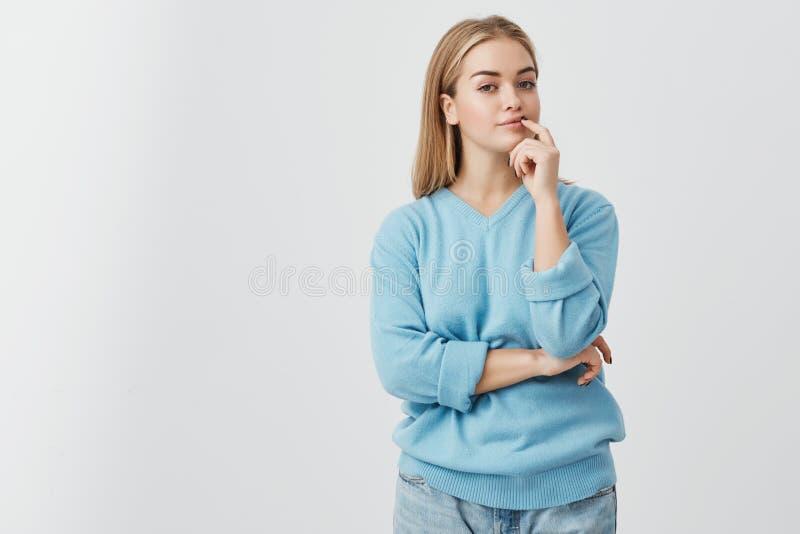 Porträt des jungen blonden europäischen Mädchens mit der gesunden Haut, die blaue Strickjacke und die Jeans betrachten Kamera mit lizenzfreies stockfoto