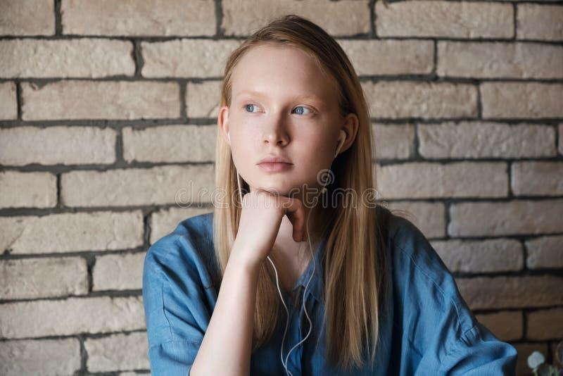 Porträt des jungen blonden Mädchens mit Kopfhörern Mädchenkopfstützen auf ihrer Hand stockbilder
