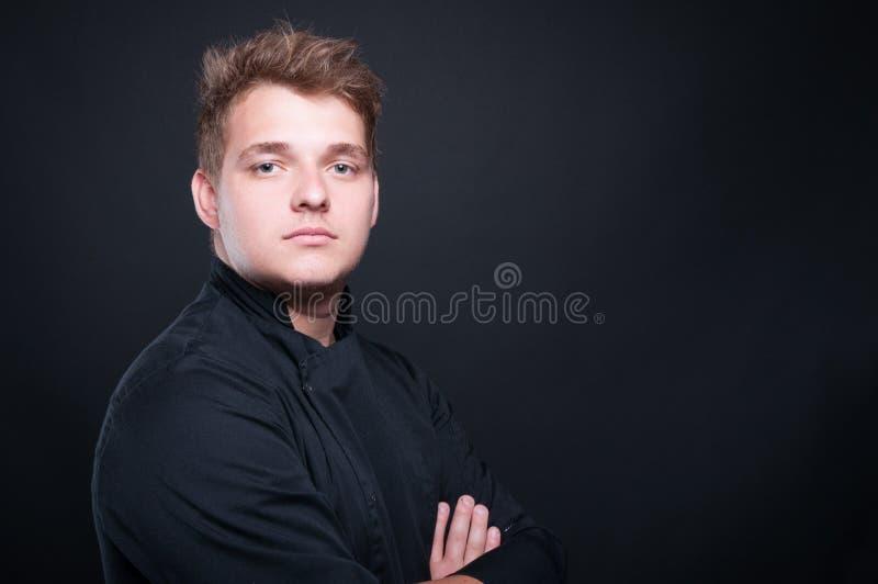 Porträt des jungen Chefs aufwerfend mit den gefalteten Armen lizenzfreie stockbilder