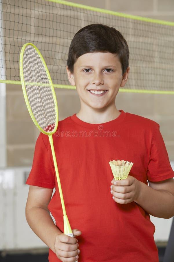 Porträt des Jungen in der Schulturnhalle, die Badminton spielt stockfoto