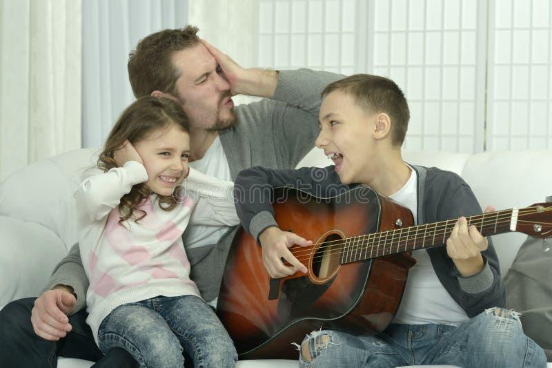 Porträt des Jungen die Gitarre für seine Familie spielend stockfotos