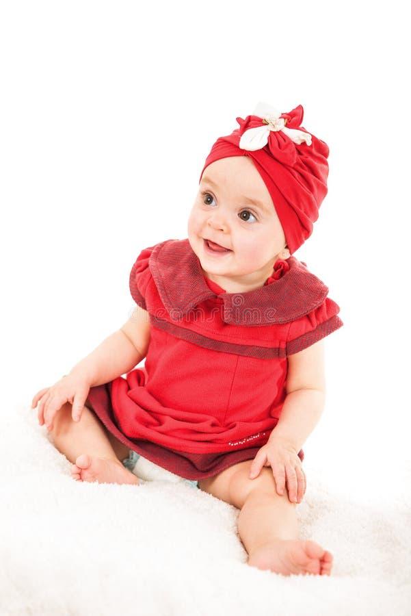Porträt des jungen einjährigen Babys im roten Kleid mit rotem Hut auf ihrem Kopf, der weg schaut lizenzfreie stockfotografie