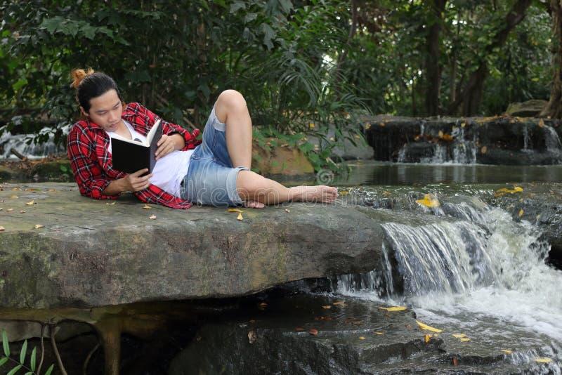 Porträt des jungen entspannten Mannes im roten Hemd, das auf dem Boden liegt und ein Buch im schönen Naturhintergrund liest stockbild