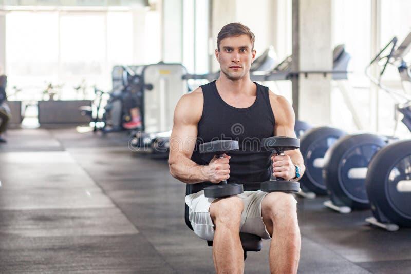 Porträt des jungen erwachsenen muskulösen errichteten hübschen Athleten, der in einer Turnhalle ausarbeitet, auf einer Gewichtheb stockfotos