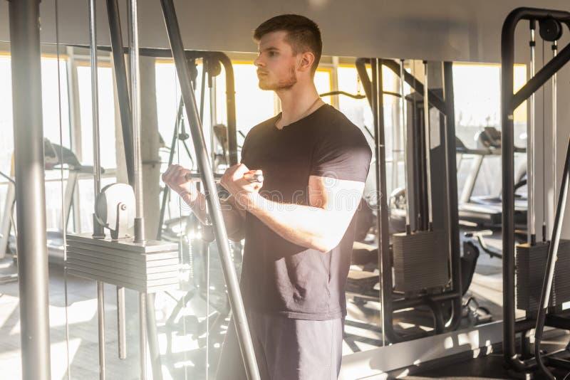 Porträt des jungen erwachsenen Sportathleten-Manntrainings an der Turnhalle allein, Gewichte in der Turnhalle stehend und anheben stockfotografie