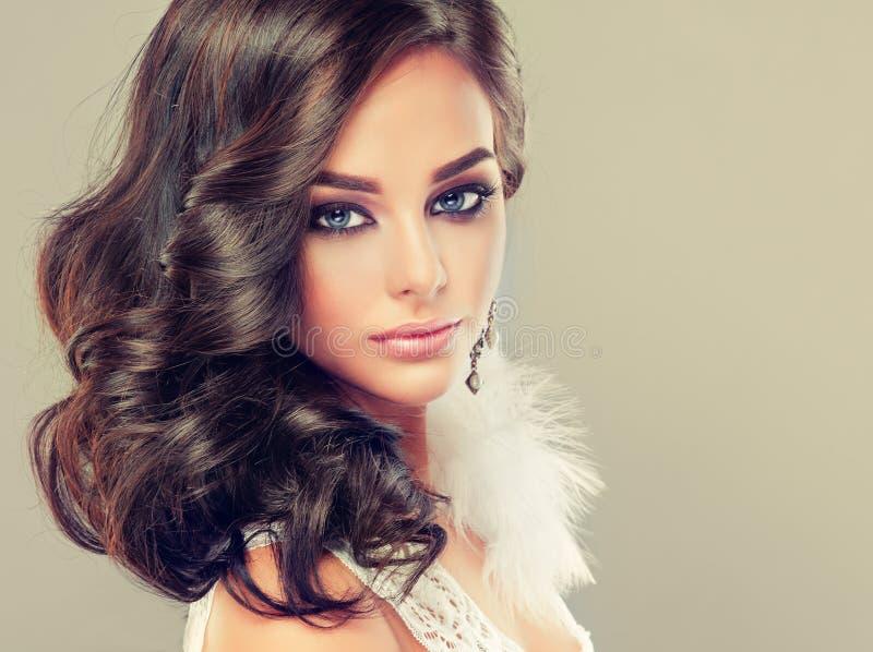 Porträt des jungen gelockten behaarten Brunette mit klarer Ostart bilden Elegante gelockte Frisuren stockbild