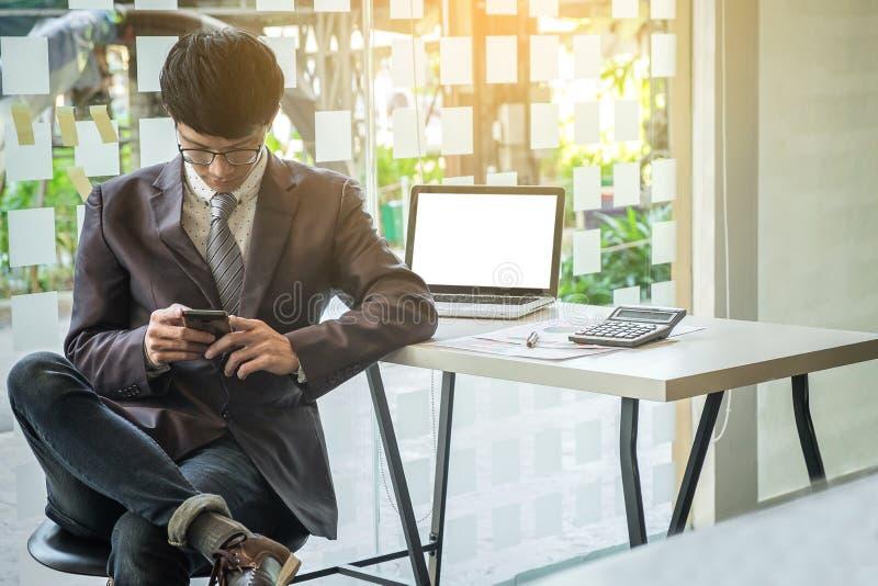 Porträt des jungen Geschäftsmannes, der intelligentes Telefon in einem Büro verwendet stockfotografie