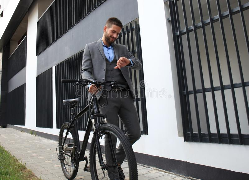 Porträt des jungen Geschäftsmannes mit seinem Fahrrad, welches die Uhr betrachtet stockfoto