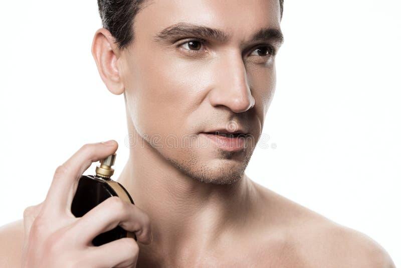 Porträt des jungen gutaussehenden Mannes aufwerfend mit Parfüm nach der Dusche am Morgen lokalisiert lizenzfreie stockfotos