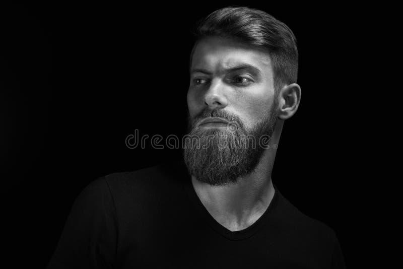 Porträt des jungen hübschen bärtigen Mannes, der vorwärts schaut stockfotografie