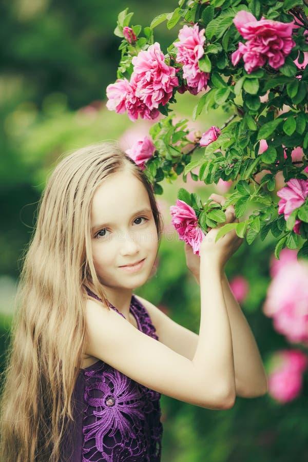 Porträt des jungen hübschen Mädchens mit dem langen hellen Haar nahe Busch mit rosa Blumen und Grün verlässt vorwärts schauen stockfotos