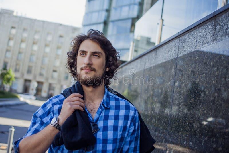 Porträt des jungen hübschen stilvollen Mannes auf der Straße Mit dem Hoodie an der Schulter lizenzfreie stockbilder