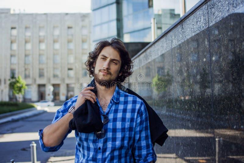 Porträt des jungen hübschen stilvollen Mannes auf der Straße Mit dem Hoodie an der Schulter stockfotografie