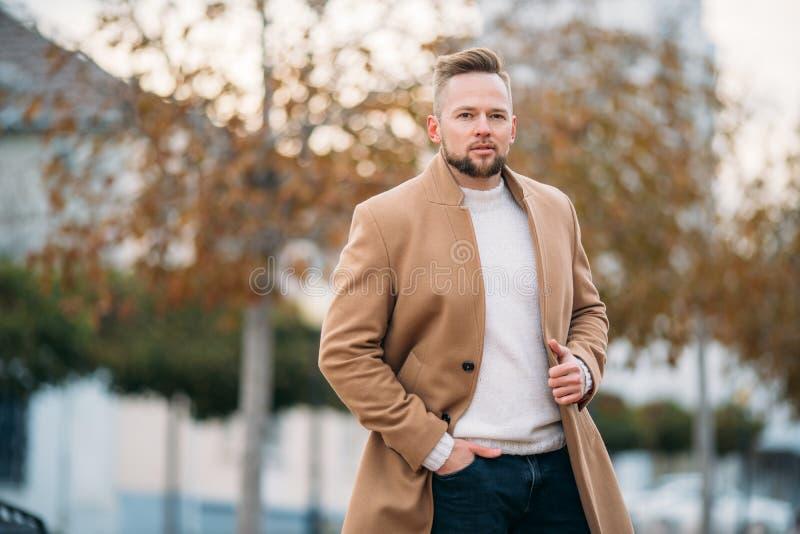 Porträt des jungen hübschen stilvollen Mannes im eleganten Mantel stockfotografie