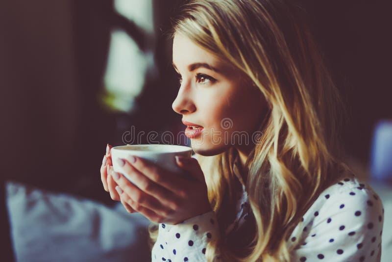 Porträt des jungen herrlichen weiblichen trinkenden Tees und aus dem Kaffeestubefenster heraus beim Genießen ihrer Freizeit t dur lizenzfreie stockfotos