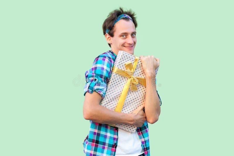 Porträt des jungen Hippie-Mannes des Vergnügens im weißen T-Shirt und in der karierten Hemdstellung und des umarmen Geschenkes mi stockfotografie