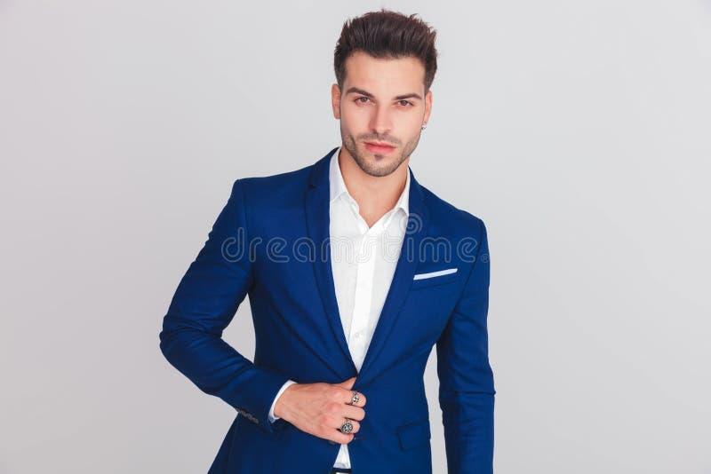 Porträt des jungen intelligenten zufälligen Mannes, der seine blaue Klage knöpft stockfotografie