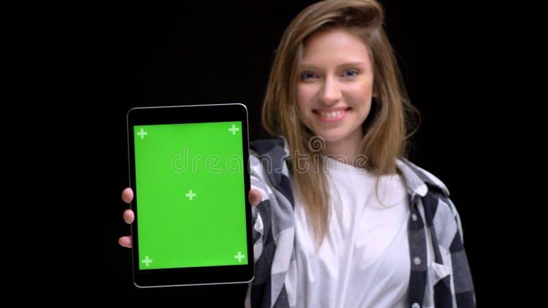 Porträt des jungen kaukasischen langhaarigen Mädchens im Hemd, das smilingly grünen Schirm der Tablette in Kamera auf Schwarzem z lizenzfreie stockfotografie