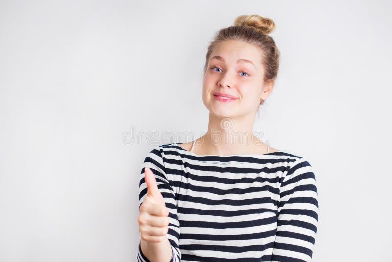 Porträt des jungen lächelnden Blondinevertretungsfingers herauf Zeichen stockfotos