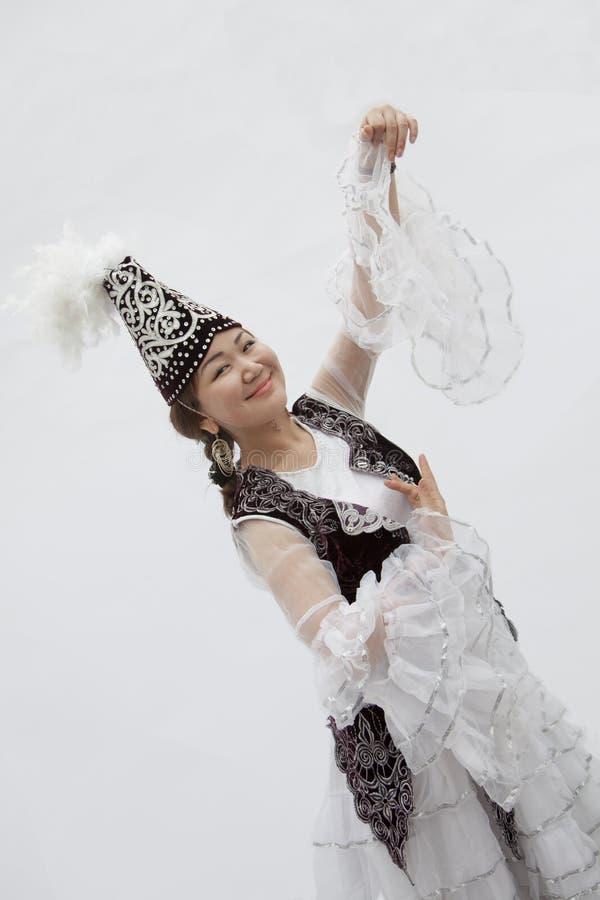 Porträt des jungen lächelnden Frauentanzens in der traditionellen Kleidung von Kasachstan, Atelieraufnahme stockbilder