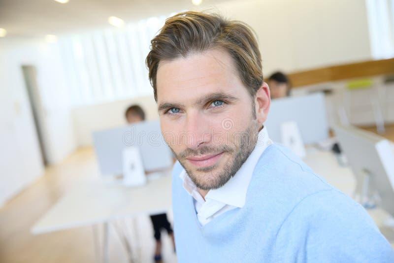 Porträt des jungen lächelnden Geschäftsmannes im Büro lizenzfreie stockfotos