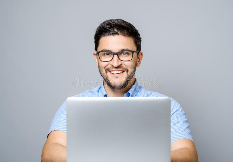Porträt des jungen lächelnden Mannes, der am Schreibtisch mit Laptop sitzt stockbild