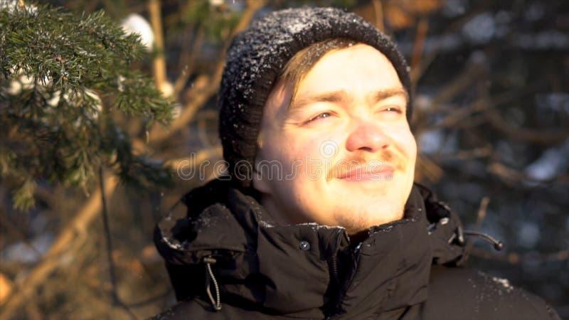 Porträt des jungen, lächelnden Mannes mit dem Schnurrbart Schneefälle im Winterwald genießend, seine Augen vom hellen Sonnenschei stockfotografie