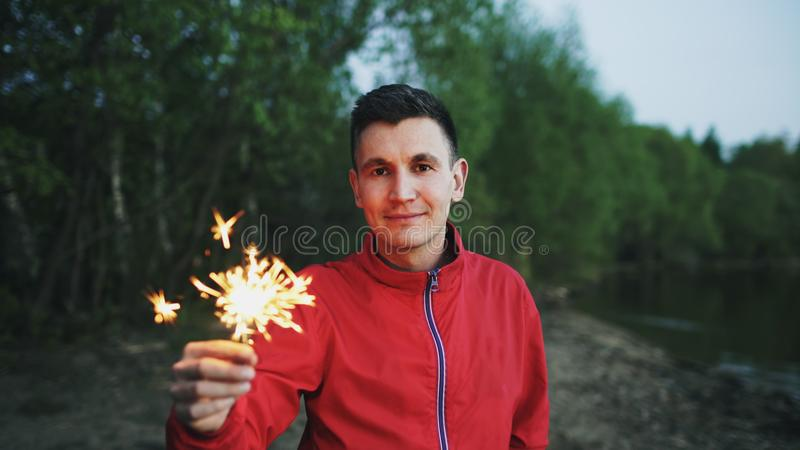 Porträt des jungen lächelnden Mannes mit Wunderkerze feiernd am Strandfest lizenzfreies stockbild