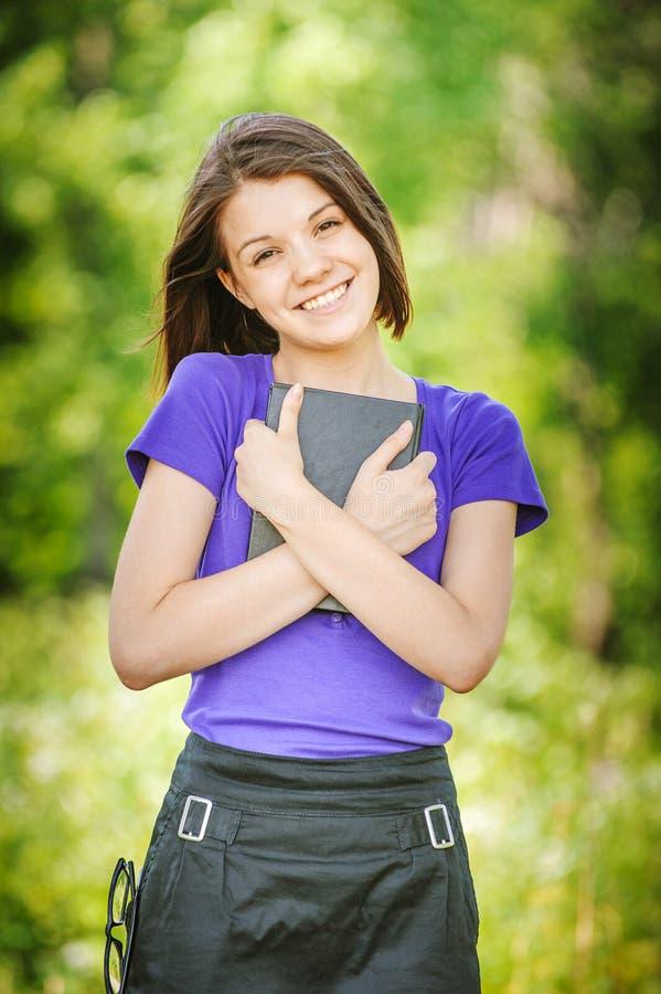 Porträt des jungen lachenden Frauenlesebuches stockfotografie