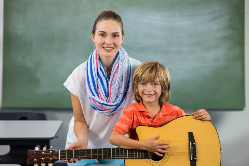 Porträt des jungen Lehrers Jungen unterstützend, um Gitarre zu spielen lizenzfreie stockbilder